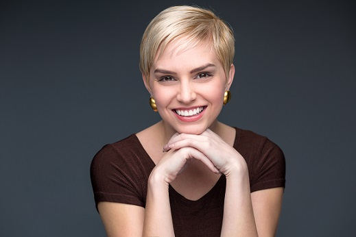 Woman with short blonde pixie cutt smiling and looking at camera