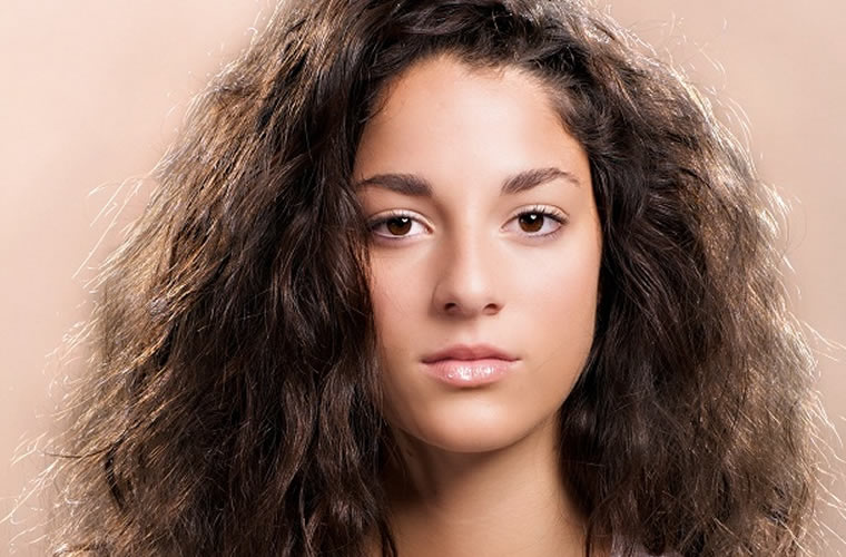 woman looking unhappy with dark and frizzy hair