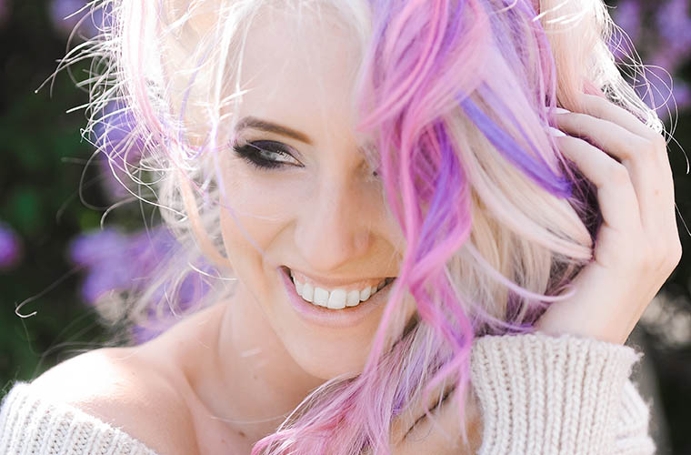 Woman with purple, pink, and blonde hair smiling