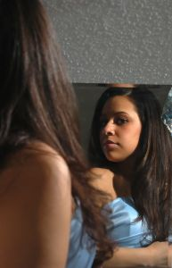 a woman looking at her hair in the mirror