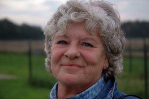 older woman with short grey hair smiling at camera