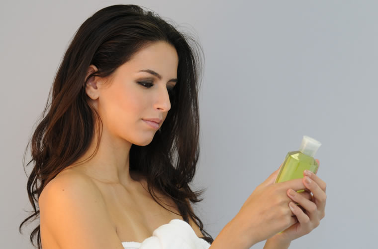 Woman with wavy brunette hair looking at a bottle of shampoo