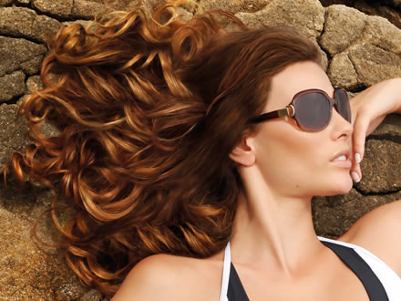 an image of a woman posing outside with long curly red hair and sunglasses