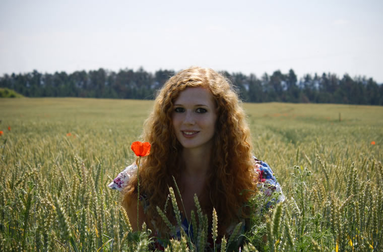 Woman with curly red hair posing in a field